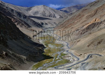 The valley of the river is among the high mountains: steep slopes a blue river flows down the gorge along the to the river the road descends Tibet.
