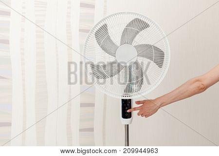 Hand presses the button on the control panel on the white electric fan