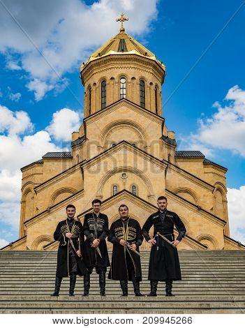 Tbilisi Georgia - June 8 2017: Groomsmen pose in front of the Metekhi Georgian Orthodox church