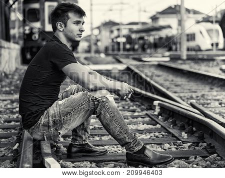 Attractive young man sitting on railroad, wearing black t-shirt and jeans, looking afar