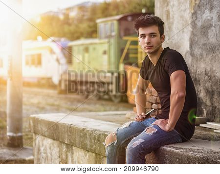 Smiling young man sitting on concrete steps. Arms resting on thighs