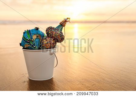 Blue Christmas Decorations collected in a white bucket at Golden Sunset on the background of Beach and Sea Winter Holiday Concept