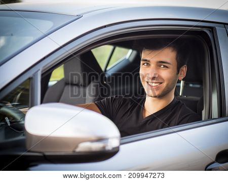 Serious young man or teenager driving car and looking at camera
