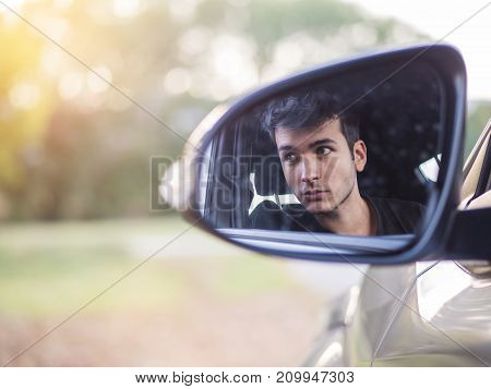 Serious young man or teenager driving car and looking at camera in the rear mirror