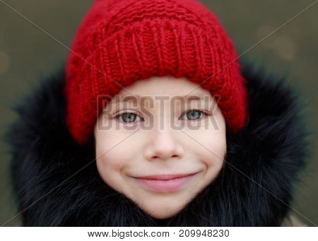 Young pretty child in red hat enjoying herself in the park. Happy childhood.