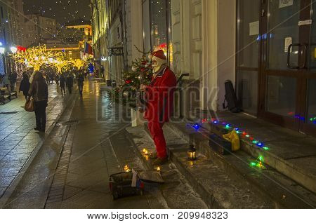 A Street Musician Dressed As Santa Claus Plays The Saxophone