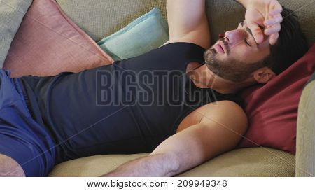 Three Quarter Shot of a Young Man Resting on the Couch in the Home Living Room.