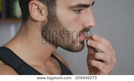 Young sexy athletic man eating almonds in kitchen, choosing a healty lifestyle