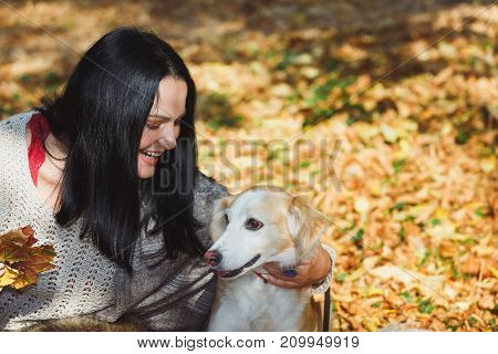 Woman embracing a cute dog in beauty in autumn scenery,shallow depth of field