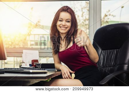 Pretty young woman working in office on computer at her desk, with a friendly attitude doing thumb up sign for OK