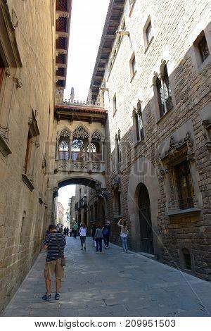 BARCELONA - JUN. 11, 2013: Carrer del Bisbe Irurita (Bishop Irurita's Street) and Neogothic style bridge by architect Joan Rubió in the Old City (Ciutat Vella) of Barcelona, Catalonia, Spain.