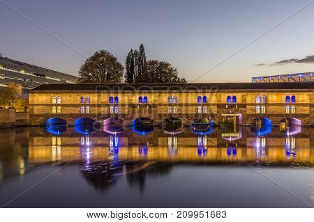 Evening view of the Barrage Vauban, or Vauban Dam, is a bridge, weir and defensive work erected in the 17th century on the River Ill in the city of Strasbourg in France