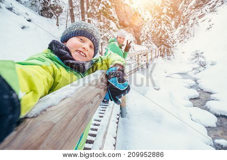 Boy take a selfie picture with his father in snow mountain canyo