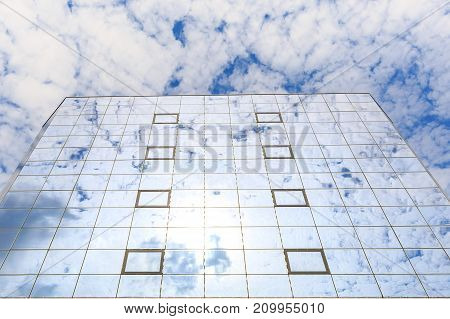 Blue clouds are reflected in the glasses of windows of a modern building. Bottom view