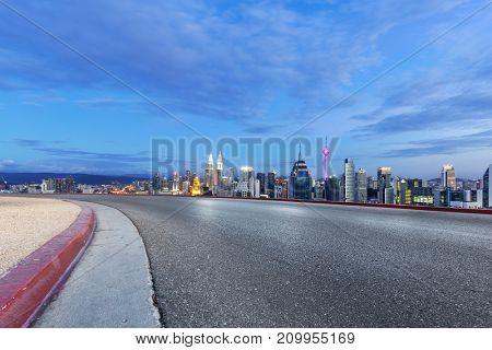 empty asphalt road and cityscape of kuala lumpur at twilight