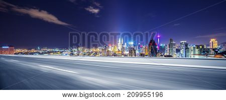 blurry empty asphalt road and cityscape of kuala lumpur at night