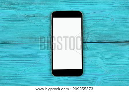 Mobile phone with blank screen mock up isolated on blue wood table background. Smartphone on wood table. Smartfone white