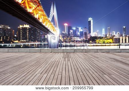 empty wooden floor and modern suspension and cityscape of chongqing at night