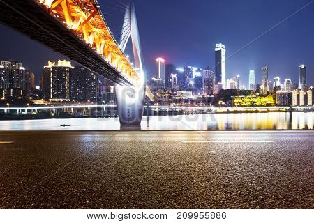empty asphalt road and suspension bridge and cityscape of chongqing at night