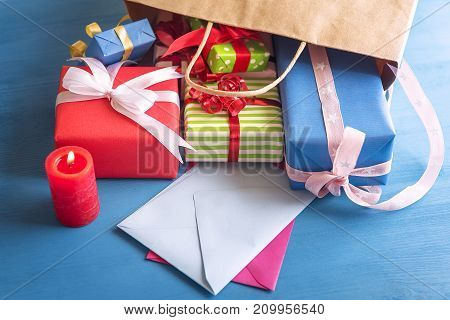 Many and colorful presents spilled out of a bag on a blue wooden table falling over empty envelopes near a lit red candle.