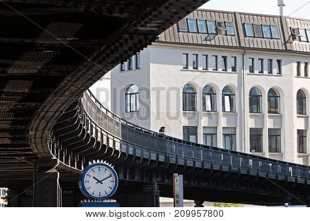 clock under the curve of a suburban railway bridge in the city of Hamburg Germany traffic concept selected focus