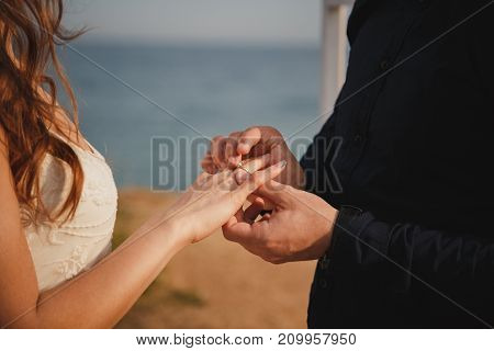 Man Is Putting Wedding Ring On His Bride's Hand, Close Up. Outdoor Beach Wedding Ceremony, Stylish G