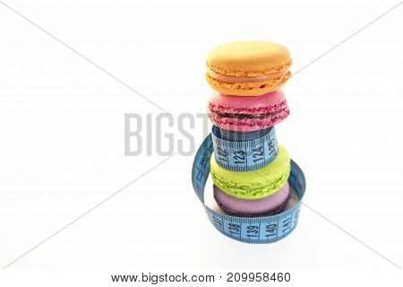 Colorful macaroons and blue meter tape, concept of healthy eating and nutrition