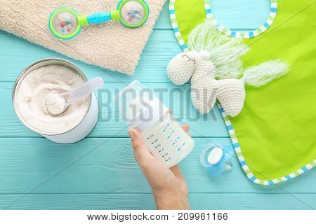Woman holding feeding bottle of baby milk formula on wooden background