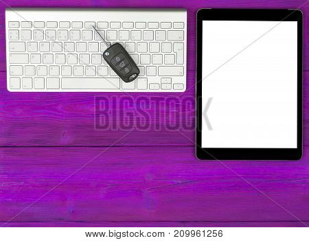 Business Workplace with wireless keyboard tablet computer and car keys on pinkwooden background. Office desk with copy space. Empty space for text