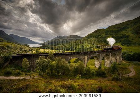 Jacobite steam train on old viaduct in Glenfinnan with mountains and Loch Shiel in background Scotland