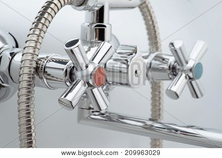 Mixer cold hot water on a white background. Focus on the valve with the hot water. Chrome plated metal.