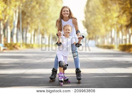 Mother with daughter rollerskating in park