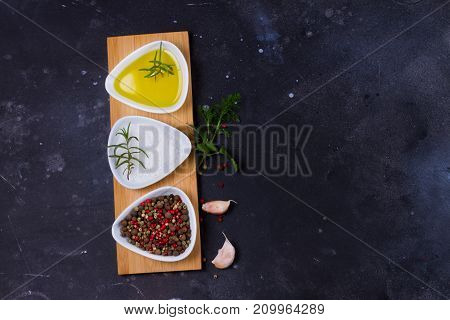 Food background - spices with olive oil on black background