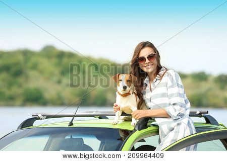 Beautiful young woman with cute dog near car on river shore