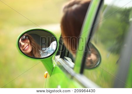 Young woman looking in car side mirror