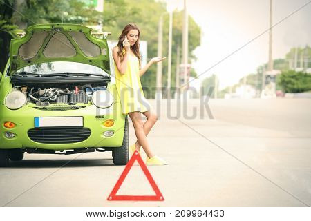 Upset young woman with cell phone near broken car