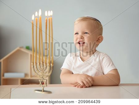 Cute boy sitting near nine-branched menorah on table at home