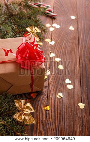 Christmas gift on a wooden brown table. Branches of spruce and confetti. Close-up. Concept of holidays, christmas.