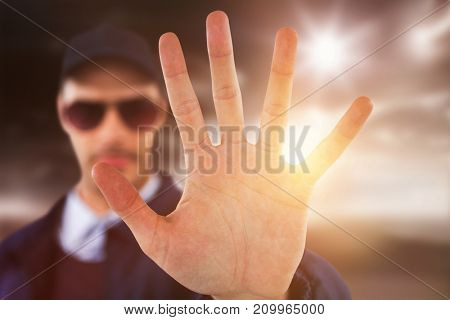 Confident security officer making stop gesture against open road