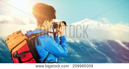 Hiker with backpack taking picture against snowy mountain range against blue sky