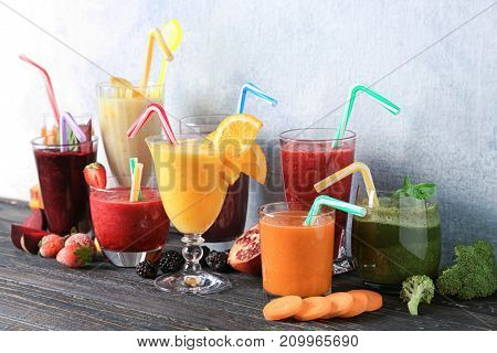 Glassware with different smoothies on table against light background