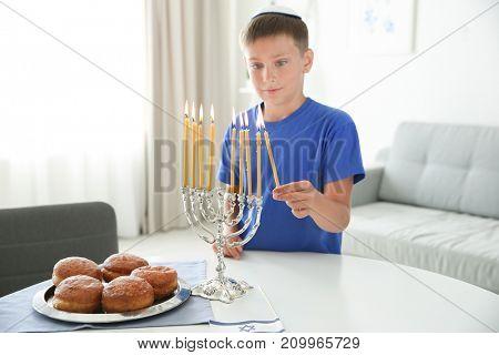 Jewish boy lightning menorah at home