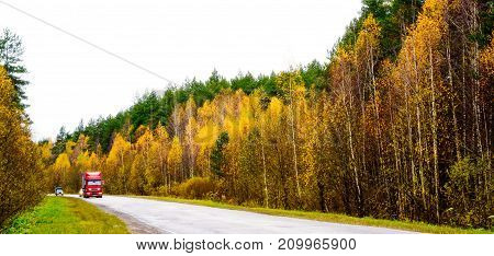 Asphalt road through the autumn forest with a red truck.