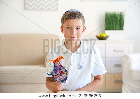Jewish boy with handmade jug at home