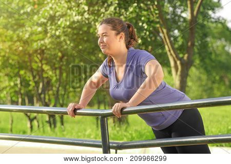 Overweight young woman exercising in park. Weight loss concept