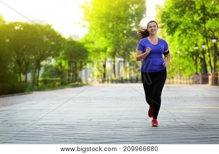 Overweight young woman jogging in park. Weight loss concept