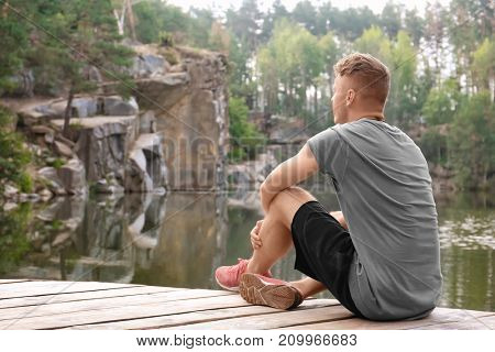 Young man sitting near lake in forest
