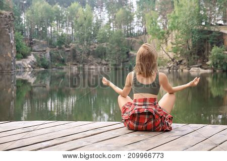 Young beautiful woman sitting near lake in forest