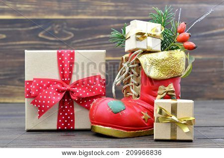Christmas boot and Christmas gifts on wooden background