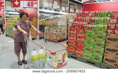 Grandma (my mother) pushing a shopping cart at Makro Sainoy branch Bangbuathong provice Thailand Asia 17 October 2017 12: 54 PM.